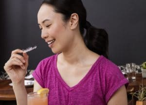 Woman taking out her Invisalign to eat