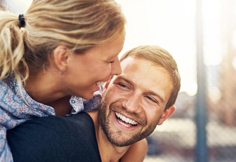 Couple embracing smiling with straight teeth